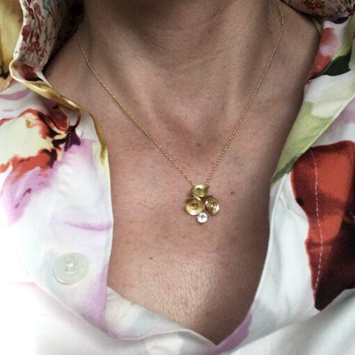 Roosjes hanger 18 k goud met 3 roosjes en witte saffier aan ankercollier Nicoline van Boven